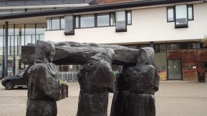 Statue of monks carrying St Cuthbert's body, outside the library: Durham.