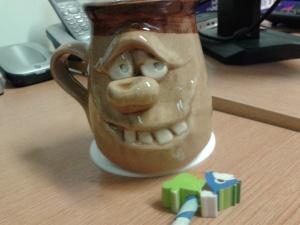 Mug, with strange pencil topper: rhino? with a mane??