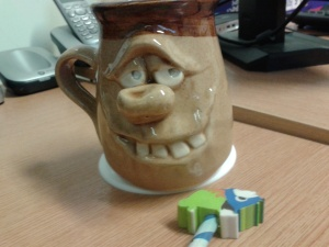 Mug, with strange pencil topper: rhino? with a mane??
