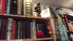 Tom the tomato contemplates books, whilst Rodin's Thinker contemplates Tom.
